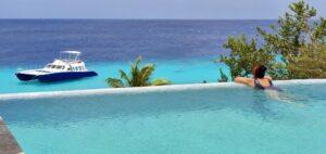 Toerist staart naar de zee in een overloopzwembad op Curaçao.