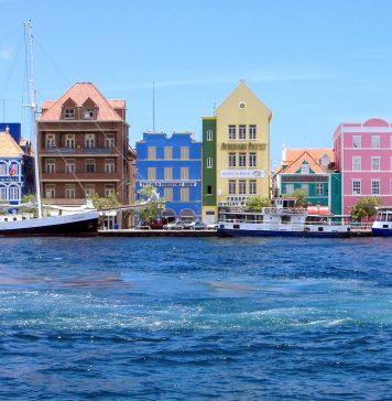 De kleurrijke gebouwen in de stad Curaçao, Willemstad. Met boten die in de oceaan varen.