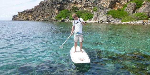 Toerist die aan het genieten is van zijn SUP tour op Curaçaose wateren.